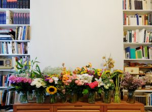 An installation shot of several bouquets sitting in glass jars on a wooden table. Behind them, a blank white wall flanked by inset bookshelves lined with books and other personal ephemera.