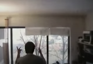 Image Description: Mel Baggs from behind, looking out a window with raised hands and moving their fingers.