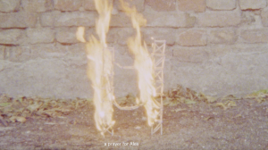 A grainy film still of the bottom of an exterior wall, with a small wooden structure on the soil which is on fire. Subtitles read: 'A prayer for Alex'.