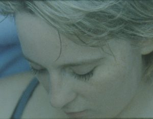 A still from the 16mm film. A close-up of Abi's face, who is a white fair-haired woman, looking downwards calmly. A bit of blue blow up pool is visible behind her, which she appears to be inside.